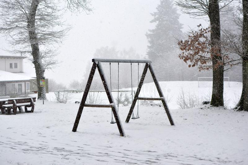 Houten schommeling op een bosdiespeelplaats in sneeuw in de winter wordt behandeld stock afbeelding