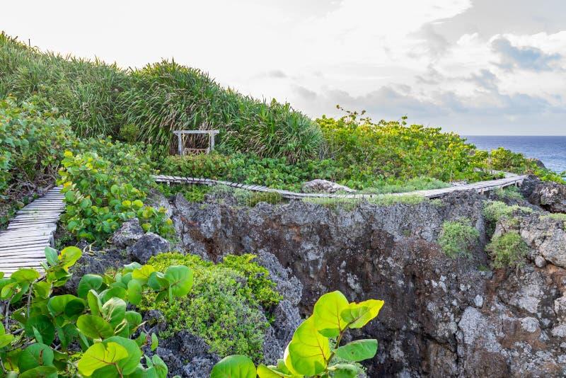 Houten sleepweg aan de kant van de bergklip door de oceaan Toneel openluchtberghelling die in vreedzaam platteland plaatsen royalty-vrije stock foto's