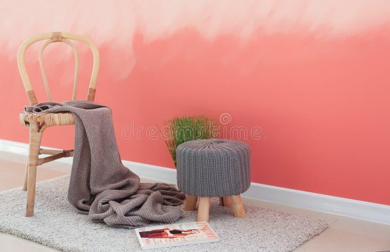 Houten stoel met ottomane dichtbij roze muur royalty-vrije stock afbeeldingen