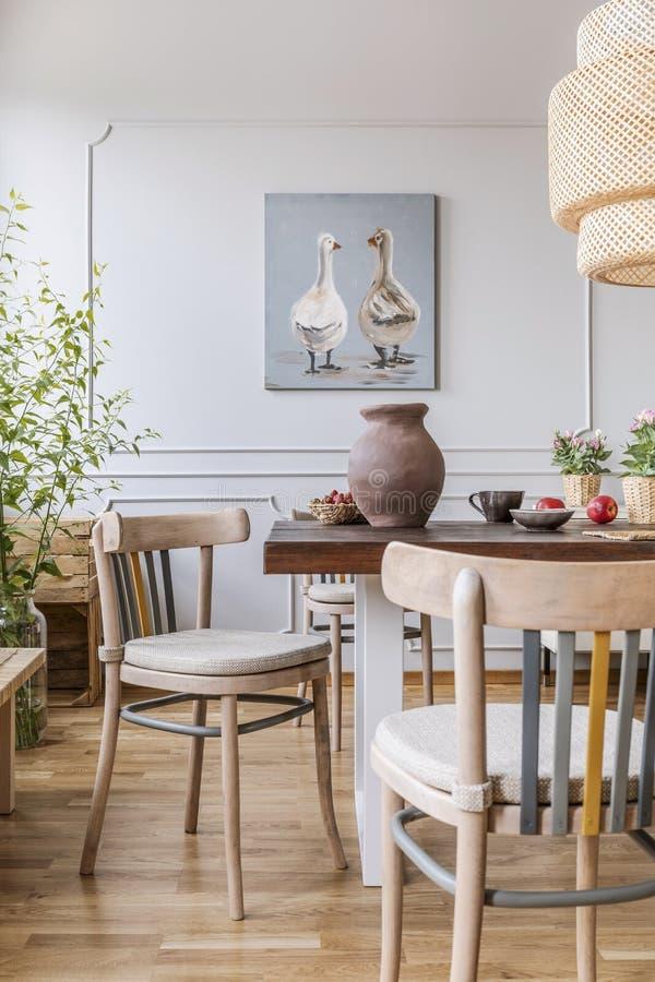 Houten stoelen bij lijst in natuurlijk wit eetkamerbinnenland met affiche en lamp Echte foto stock afbeelding