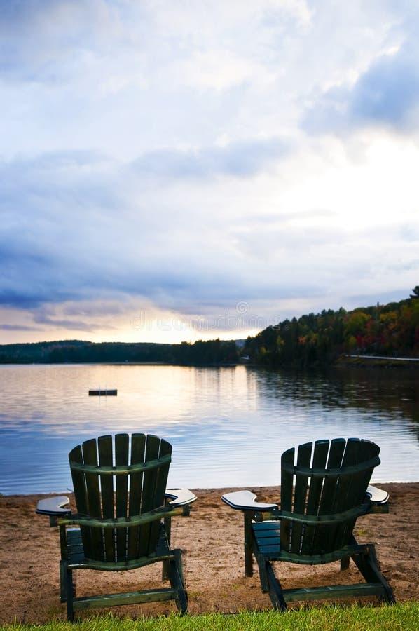Houten stoelen bij zonsondergang op strand stock afbeelding
