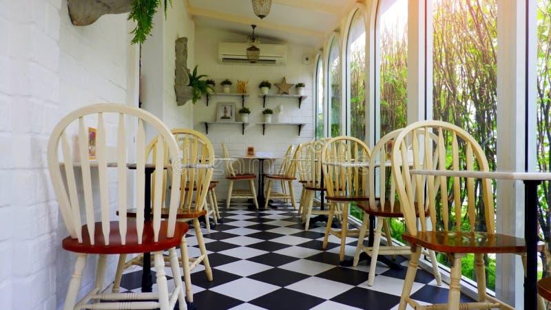 Houten stoelen en lijst in het restaurant met ochtendzonneschijn stock foto