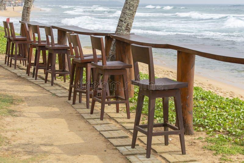 Houten stoelen en lijst in lege koffie naast het overzees op het tropische strand, Sri Lanka Sluit omhoog stock foto's