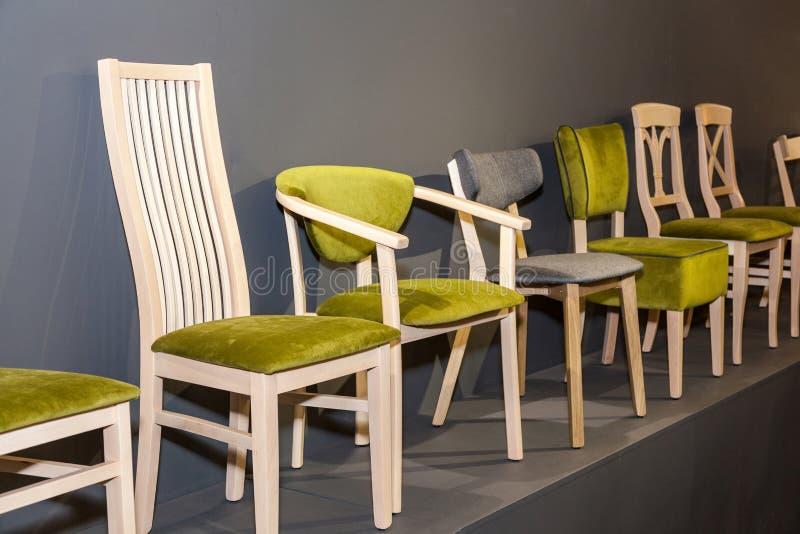 Houten stoelen met groen bekleed dichtbij grijze muur stock foto