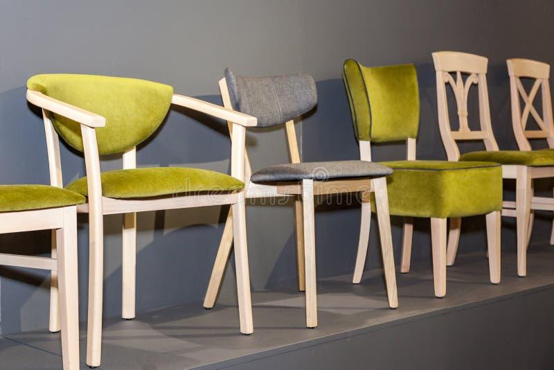 Houten stoelen met groen bekleed dichtbij grijze muur vector illustratie