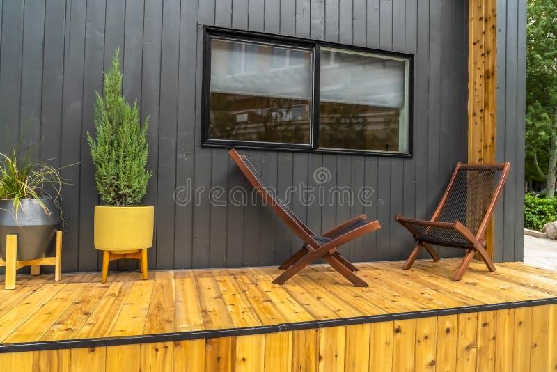 Houten stoelen op de portiek van een huis voor een grijze muur en een glijdend venster stock foto's