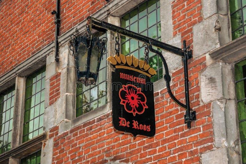 Houten straatteken van het Museum van Roos en baksteenhuis in typische stijl in Geertruidenberg stock fotografie