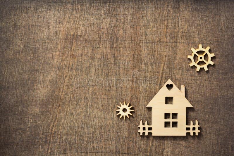 Houten stuk speelgoed huis bij houten achtergrond stock afbeeldingen