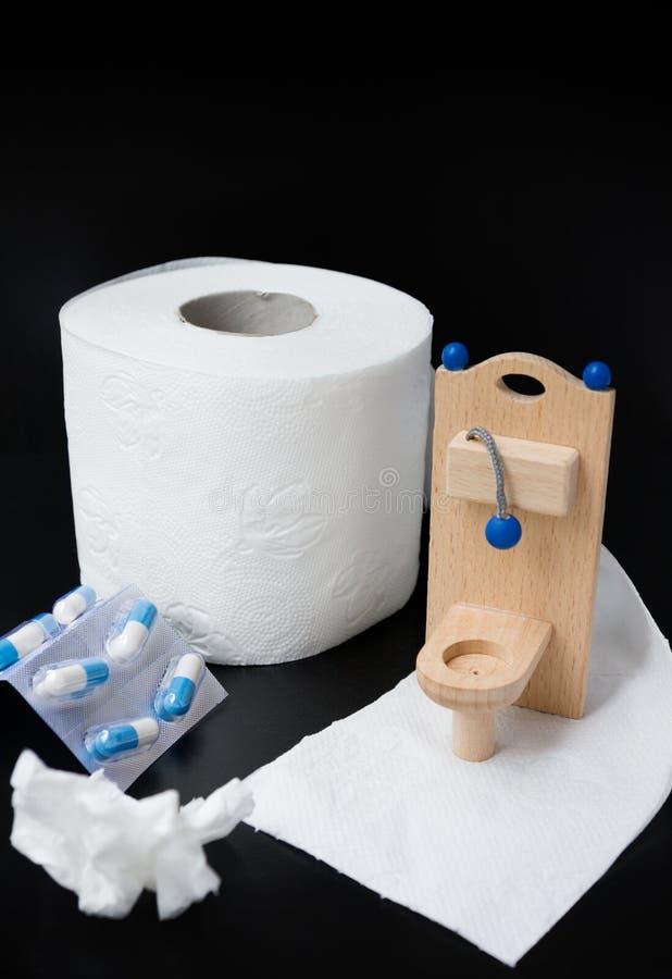 Houten stuk speelgoed toilet, pillen en document op zwarte achtergrond stock foto