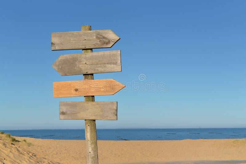 Houten tekens op een post in frint van een strand stock afbeelding