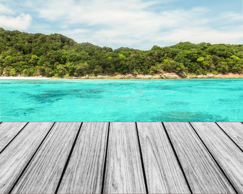 Houten Terras op het Strand met Duidelijke Hemel en Blauw Overzees en Eiland stock afbeeldingen