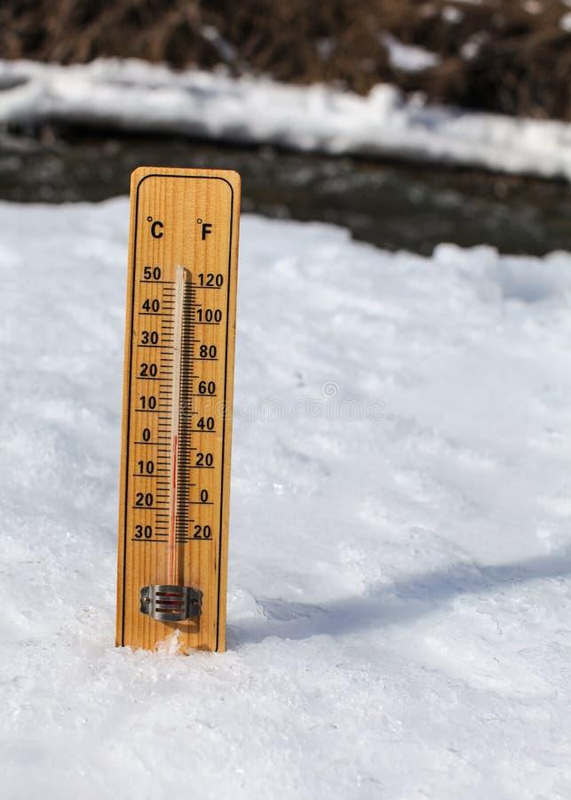 Houten thermometer die zich in ijs op gedeeltelijk bevroren rivier, zon het glanzen bevinden, die +3 graden tonen Beeld om de win stock foto's