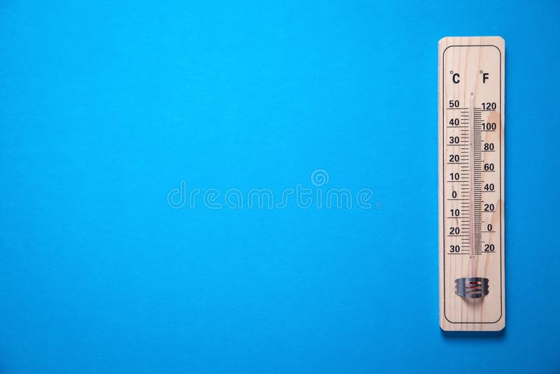 Houten thermometer op blauwe achtergrond stock afbeeldingen