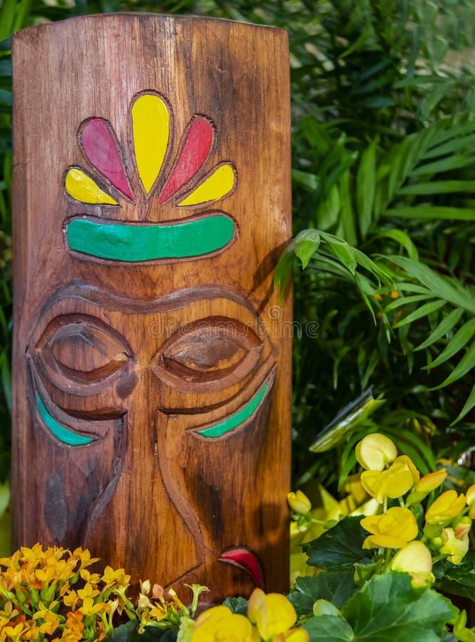 Houten tikihoofd met gesneden eigenschappen en geschilderde die accenten door bloemen worden omringd en tropisch groen - selectie stock afbeelding