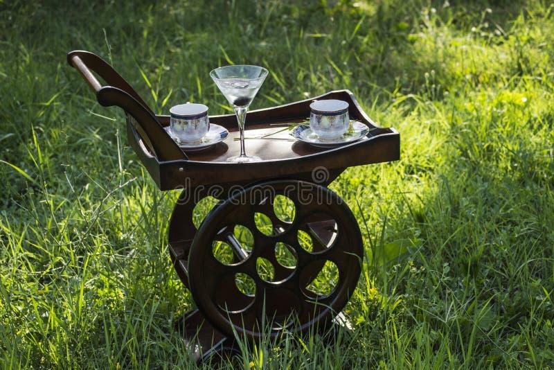 Houten Tray With Wheels And Coffee-Koppen en Martini-Glas in de Aard stock foto's