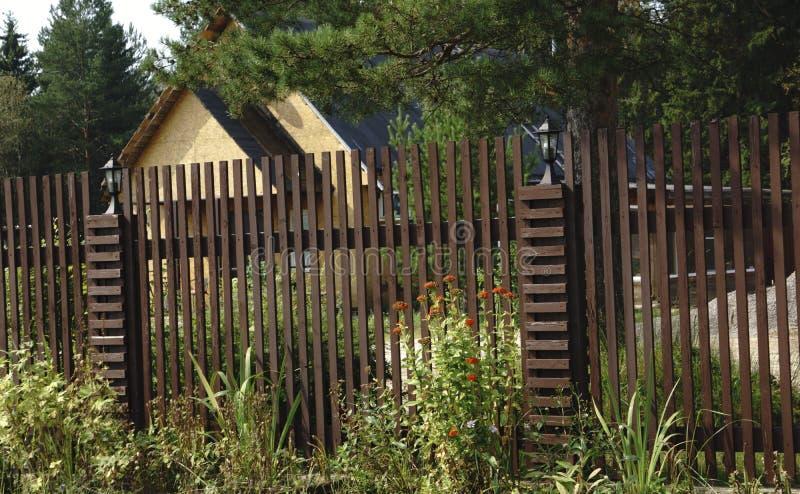 Houten tuinomheining met steen bedekte pijlers die privé-bezit bewaken Omheining van horizontaal houten planken en binnenplaatsga stock fotografie