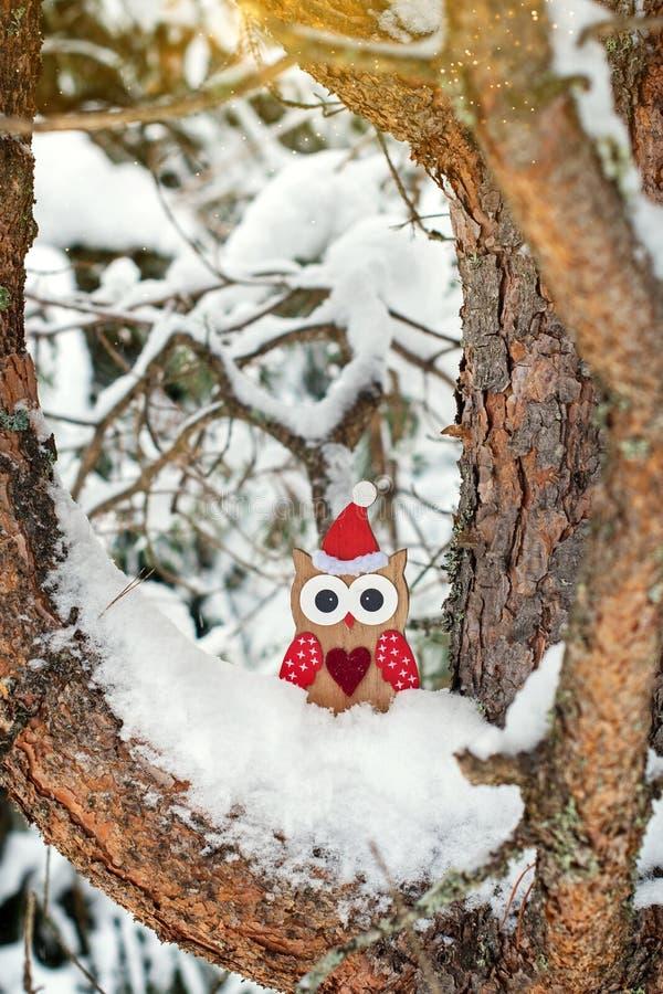 Houten uilstuk speelgoed in Kerstmankostuum op snow-covered pijnboomboom royalty-vrije stock foto's