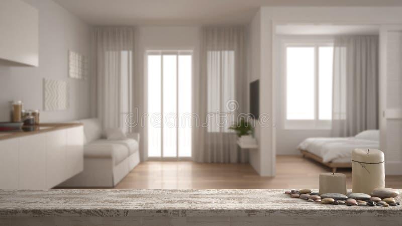 Houten uitstekende lijstbovenkant of plank met kaarsen en kiezelstenen, zen stemming, over vaag flatje met keuken, woonkamer en B stock afbeeldingen
