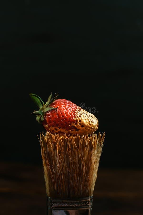 Houten varkenshaar het schilderen borstel met gouden verf en rode verse aardbei op zwarte achtergrond Donkere zeer belangrijke, m royalty-vrije stock afbeeldingen