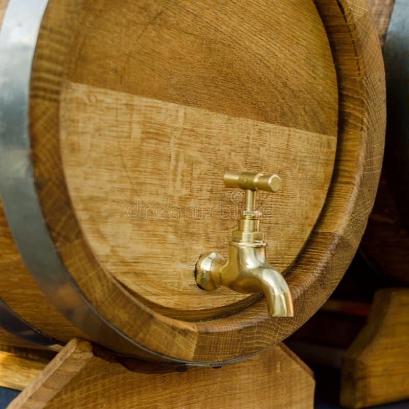 Houten vaten voor wijn met een kraan van geel metaal stock foto's