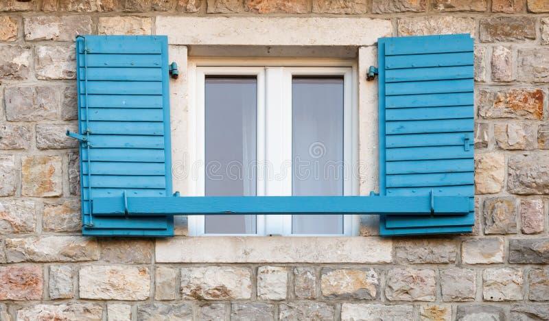 Houten venster met blauwe open jaloezie royalty-vrije stock afbeeldingen