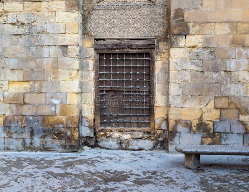 Houten venster met verfraaid ijzernet over steenbakstenen muur en marmeren tuinbank royalty-vrije stock afbeelding