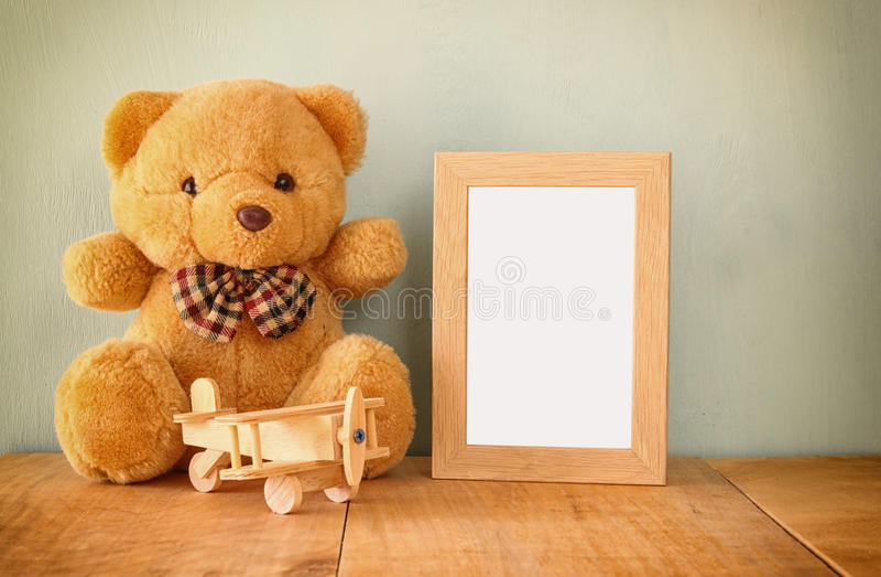 Houten vliegtuigstuk speelgoed en teddybeer over houten lijst naast leeg fotokader retro gefiltreerd beeld klaar om fotografie te stock afbeelding
