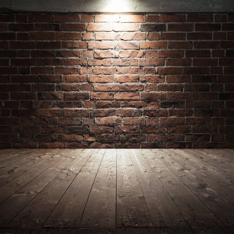 Houten vloer en rode bakstenen muur met vleklicht royalty-vrije stock fotografie