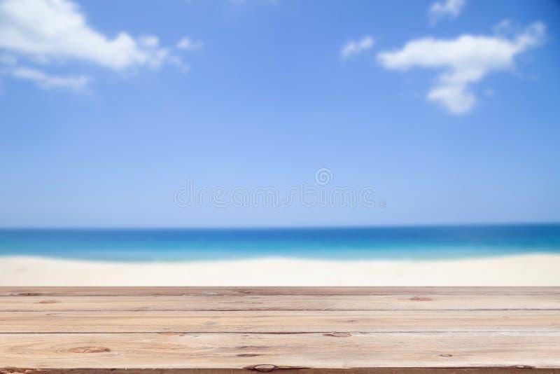 Houten vloer op onduidelijk beeld duidelijke hemel en de Zomerachtergrond van het eilandstrand stock fotografie