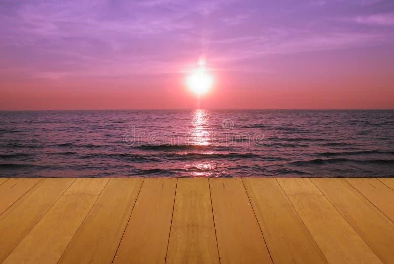Houten vloer op overzees die met purpere zonsondergang het mooie natuurlijke tropische overzees van Skie branden stock afbeelding