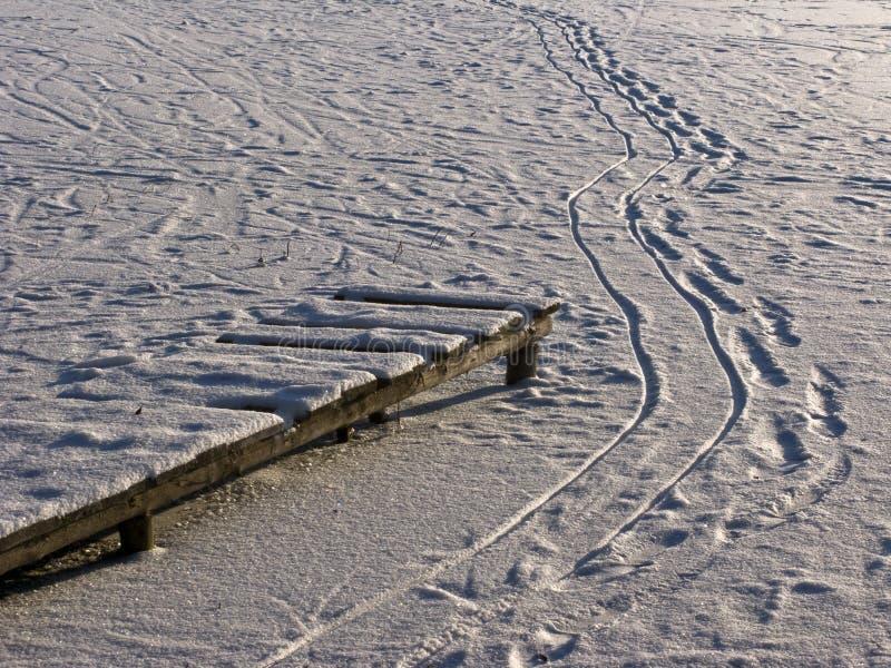 Houten voetpad en voetstappen op bevroren vijver royalty-vrije stock foto's