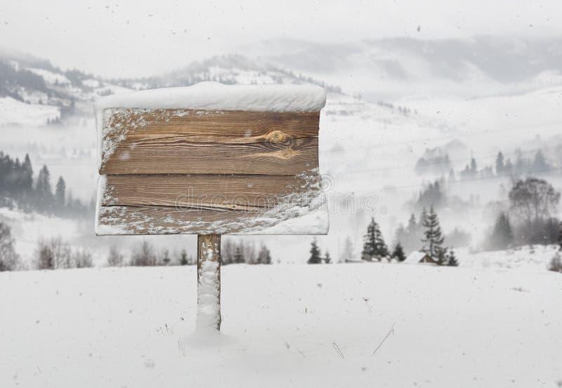 Houten voorzie met sneeuw en bergen van wegwijzers stock foto's