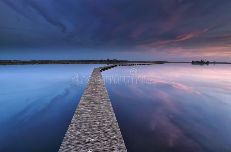 Houten walkpath op water bij dageraad stock fotografie
