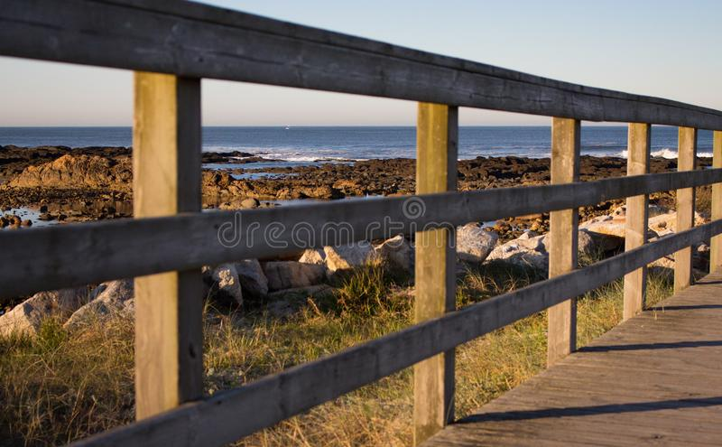Houten weg met omheining aan het strand Gang op kust in de ochtend De kust van de Atlantische Oceaan in Portugal stock afbeeldingen