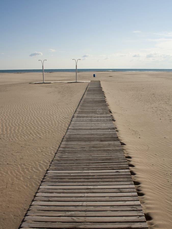 Houten weg op het zandige strand dichtbij het overzees royalty-vrije stock foto