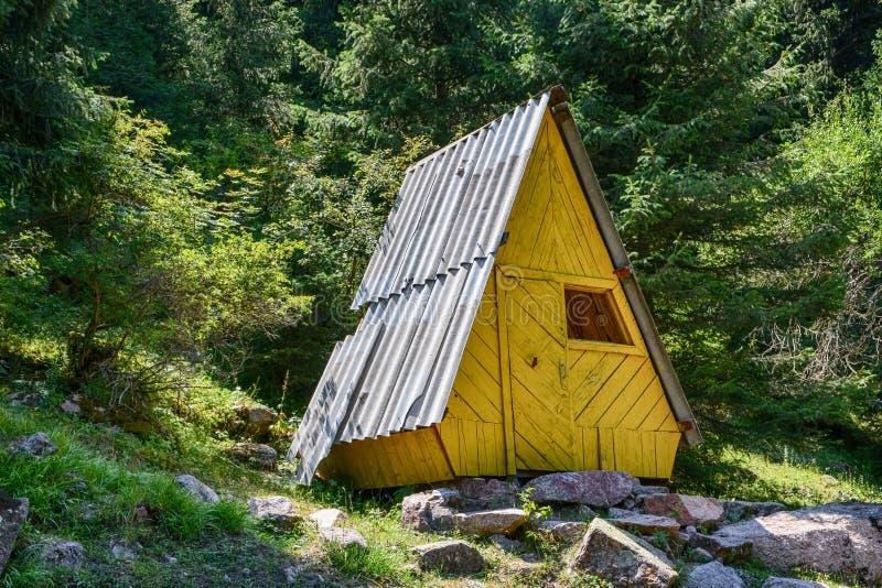 Houten weinig geel plattelandshuisje in bos royalty-vrije stock afbeeldingen