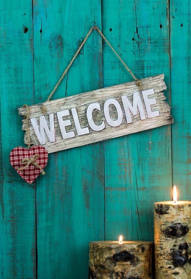 Houten welkom teken met rood hart en brandende kaarsen die op antieke wintertalings blauwe doorstane omheining hangen royalty-vrije stock afbeelding