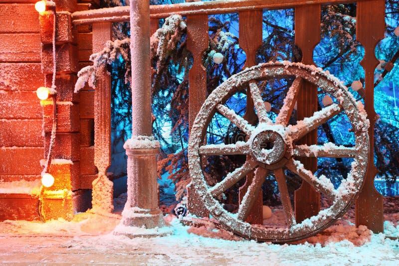 Houten wiel in sneeuwtribune dichtbij traliewerk stock fotografie