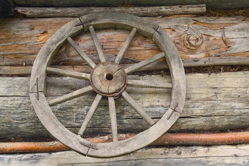 Houten wiel van een oude kar die op de muur hangen royalty-vrije stock afbeeldingen