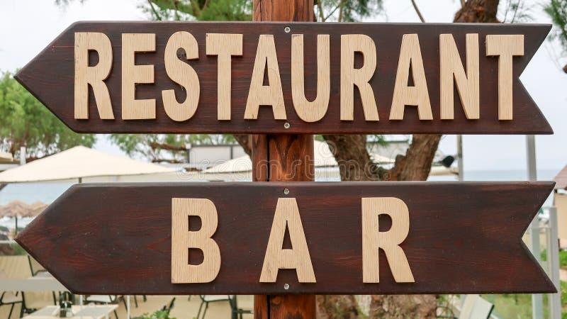 Houten wijzer aan het restaurant en de bar royalty-vrije stock afbeeldingen