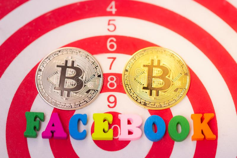 Houten woord Facebook en twee Cryptocurrency bitcoin op witte achtergrond Facebook en bitcoin stock fotografie