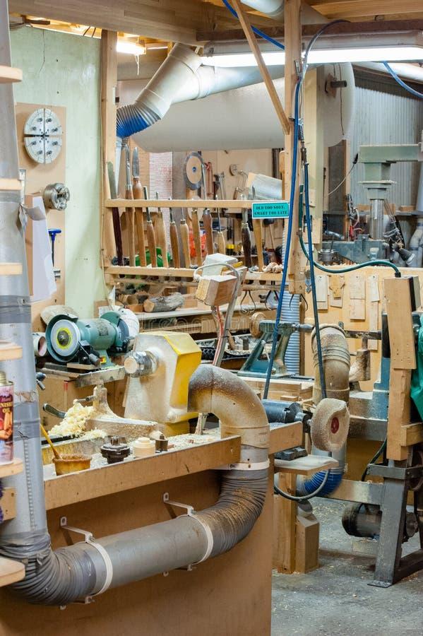 Houten workshop met stof en spaanders, hulpmiddelen en machines stock fotografie