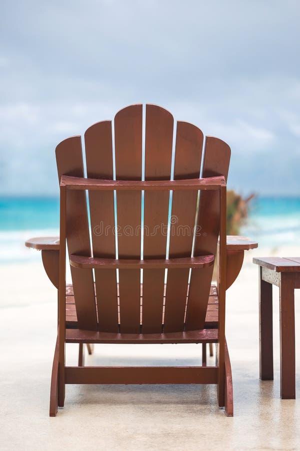 Houten zonstoel bij luxetoevlucht dichtbij Caraïbische overzees stock afbeeldingen