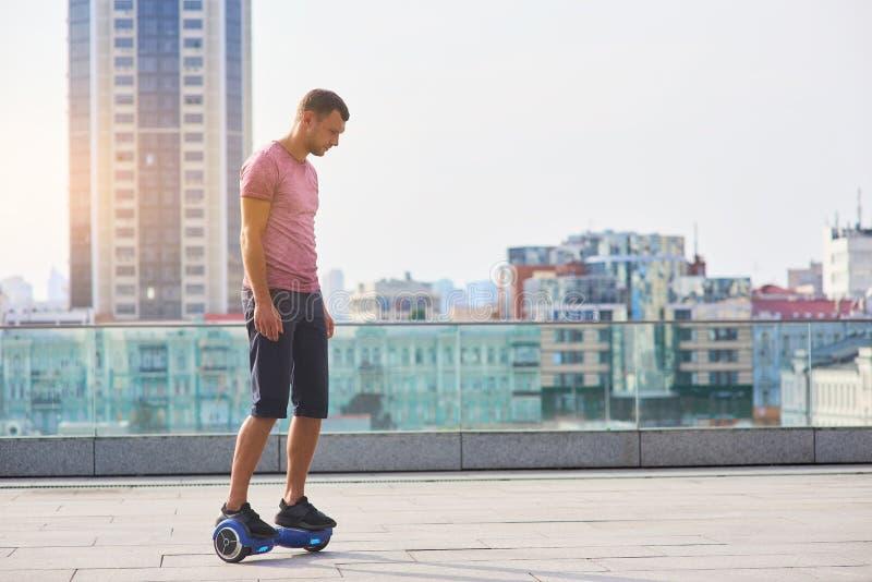 Hoverboard di guida dell'uomo, fondo della città immagini stock