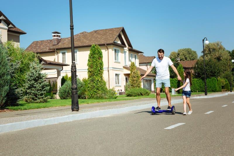 Hoverboard feliz del montar a caballo del padre así como hija fotografía de archivo