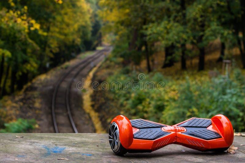 Hoverboard rosso contro lo sfondo delle rotaie della ferrovia fotografie stock libere da diritti