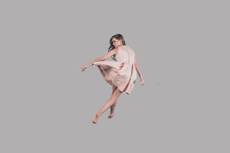 Hovering bin air. Studio shot of attractive young woman hovering in air royalty free stock image