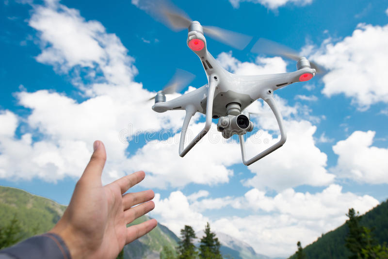 Hovering drone and a hand. Hovering drone on the blue sky background stock images