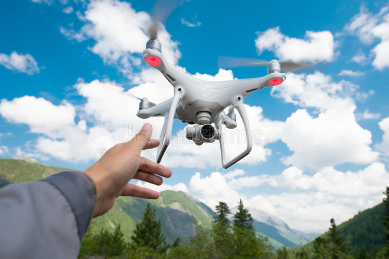Hovering drone and a hand. Hovering drone on the blue sky background stock photo