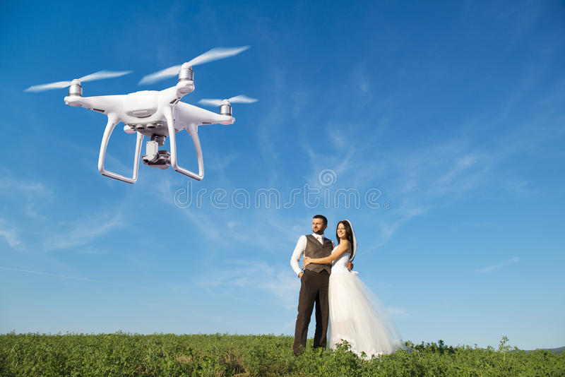 Hovering drone taking pictures of wedding couple in nature. Hovering drone taking pictures of wedding couple in summer nature stock photo